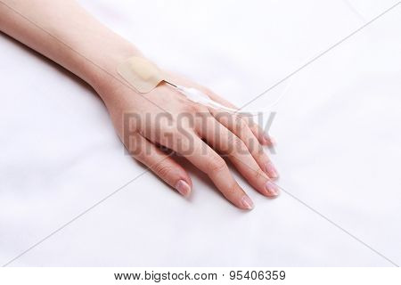 Woman hand with dropper needle on bed close-up