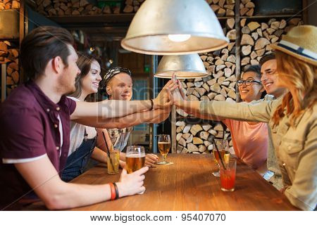 people, leisure, friendship and communication concept - group of happy smiling friends with drinks making high five gesture at bar or pub