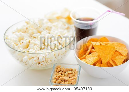 fast food, junk-food and unhealthy eating concept - close up of popcorn and corn crisps or nachos in bowls