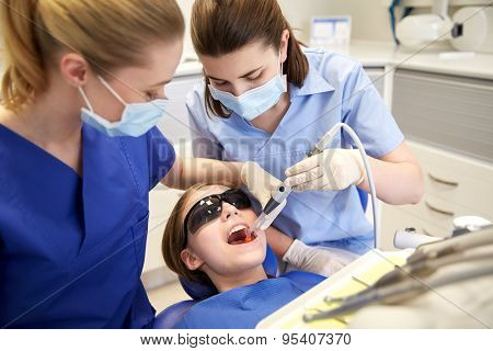 people, medicine, stomatology and health care concept - female dentists with mirror and suction treating patient girl teeth at dental clinic office