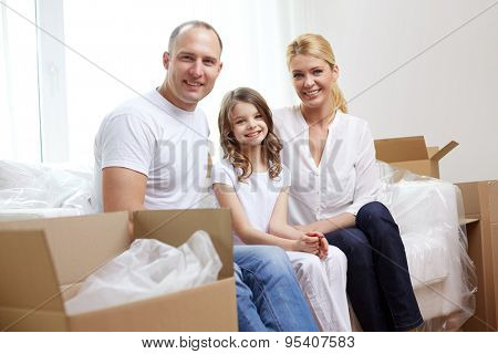 family, children, accommodation and people concept - happy family with boxes moving to new home