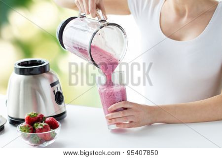 healthy eating, cooking, vegetarian food, dieting and people concept - close up of woman with blender and strawberries pouring milk shake to glass over green natural background