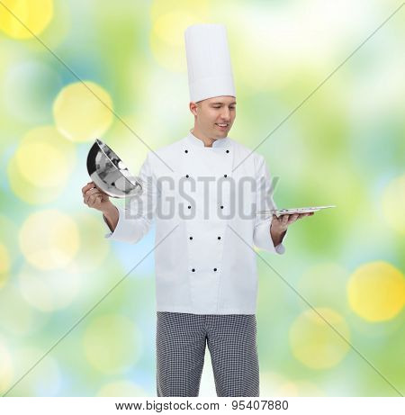 cooking, profession and people concept - happy male chef cook opening cloche cover over green lights background
