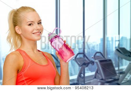 people, sport, fitness and recreation concept - happy woman drinking water from bottle over gym machines background