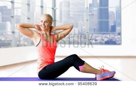 fitness, sport, exercising and people concept - smiling woman doing sit-up on mat over gym background