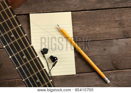 Music recording scene with guitar, memo pad and earphones  on wooden background