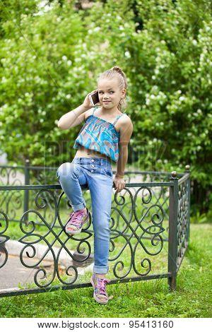 full length portrait Little girl talking on cell phone against green of Park in summer