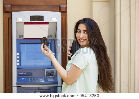 Brunette young lady using an automated teller machine . Woman withdrawing money or checking account balance