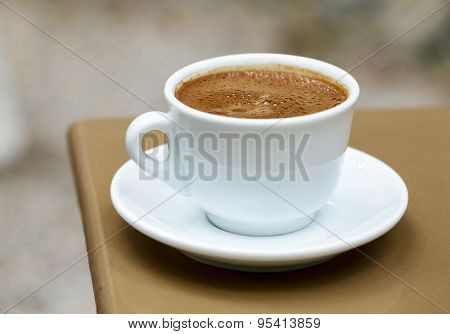 White cup with frothy greek coffee on a cafe table
