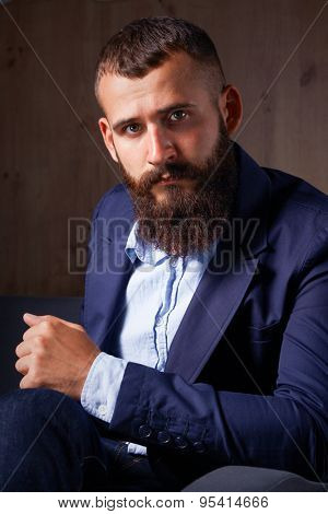 Businessman sitting on sofa in office lobby .