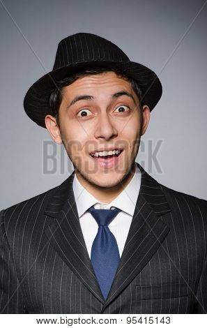 Young attractive smiling gansgter in hat and suit