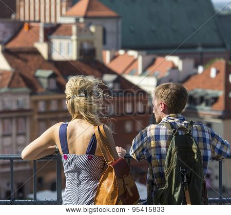 Young couple of tourists looking at the Old European Town from the observation tower, old architecture in the blur in the background.