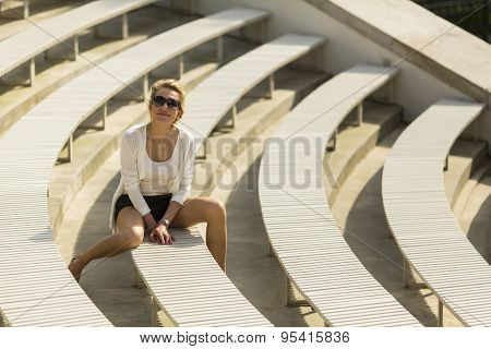 Young beautiful blondie woman sitting on benches in the Royal Baths Park in Warsaw, Poland.