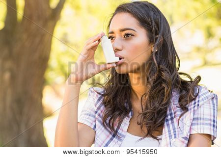 Pretty brunette using inhaler on a sunny day