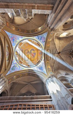 JERUSALEM, ISRAEL - MARCH 9, 2012: Gorgeous round arch ceiling in the hall in the Holy Sepulchre lit bright sun. On the ceiling of the image of Christ the Savior