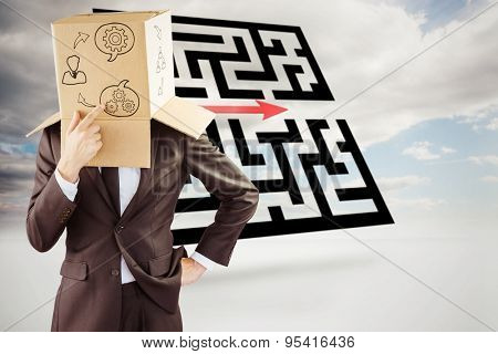 Anonymous businessman touching his chin against maze with arrow in sky
