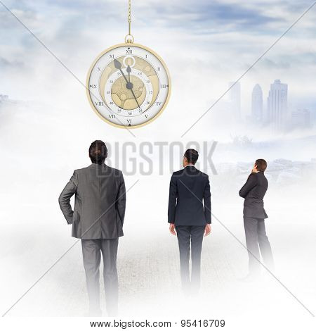 Thinking businessman touching chin against city on the horizon