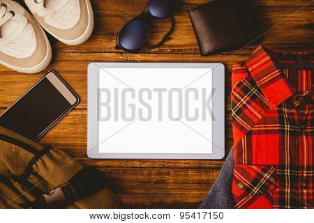 Tablet sshirt jean shoes smartphone wallet and bag on wooden table