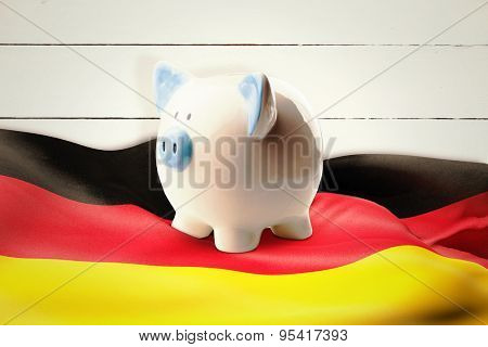 Piggy bank against painted blue wooden planks