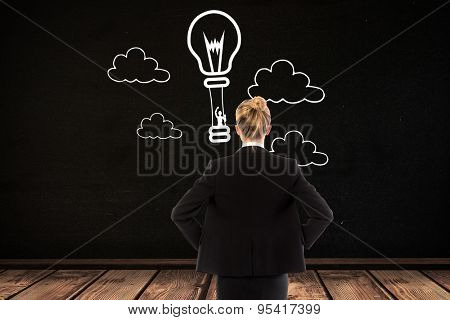 Businesswoman standing with hands on hips against black room