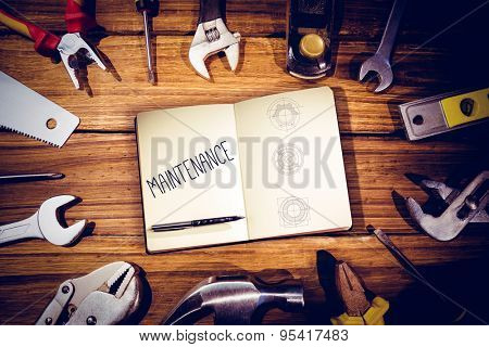 The word maintenance and notebook and pen against blueprint