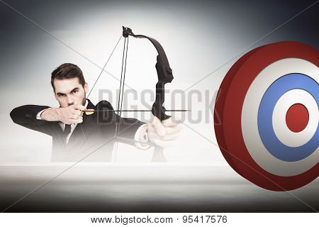Smart businessman practicing archery looking at camera against cityscape