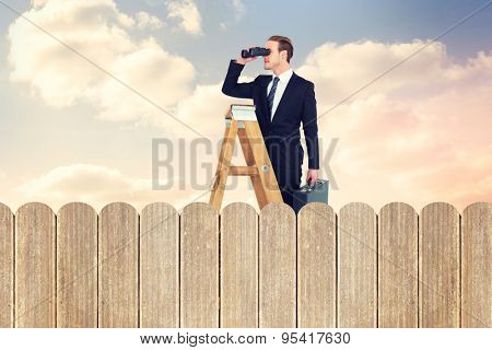 Businessman looking on a ladder against purple sky over fence