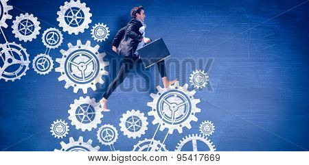 Leaping businessman against blue chalkboard