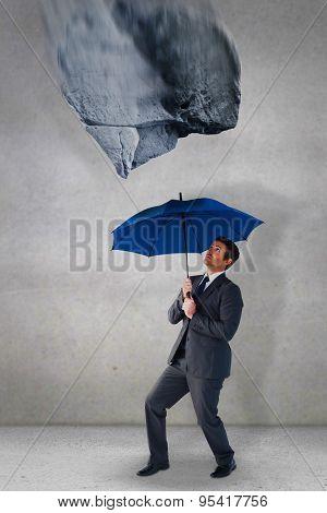 Businessman sheltering under blue umbrella against grey room
