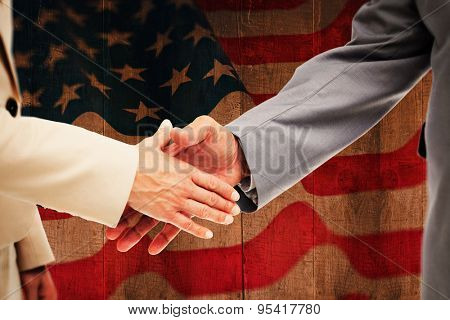 Close up of business people shaking their hands against weathered oak floor boards background
