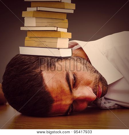 Tired businessman resting on his desk against grey vignette