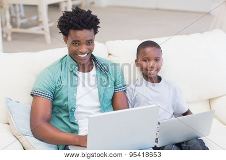 Father and son using laptops on the couch at home in the living room