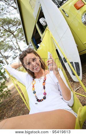 Cheerful woman relaxing in chair by camper van