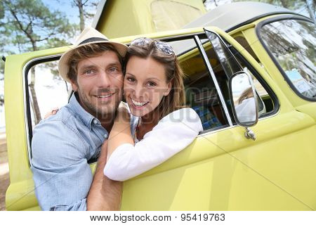 Couple standing by vintage camper van window