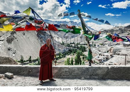 LAMAYURU, INDIA - SEPTEMBER 10, 2011: Buddhist monk standing outside with lugta prayer flags in Lamayuru gompa Buddhist monastery in Ladakh, India