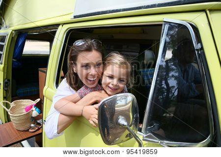 Woman with little girl sitting at camper van window