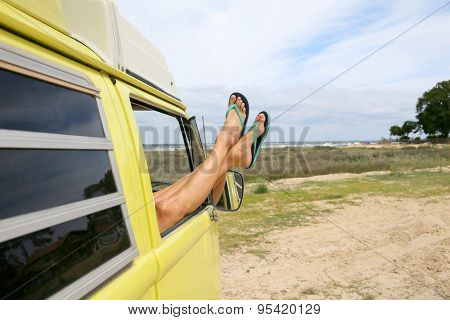Closeup of woman's feet relaxing by camper van window