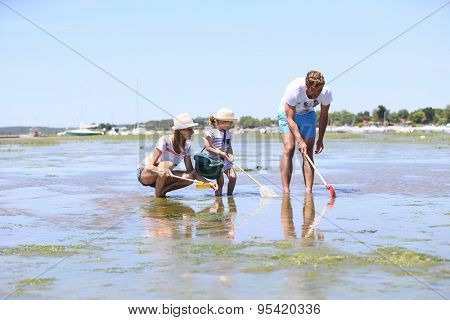 Family practicing recreational beach fisheries
