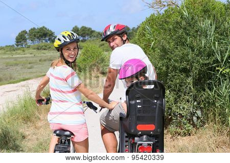 Portrait of happy family riding bikes on a sandy path