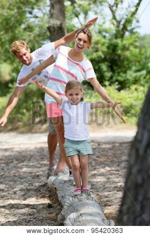 Family having fun walking on a tree trunk