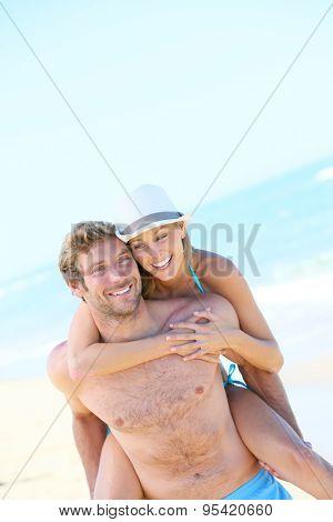 Man giving piggyback ride to girlfriend on the beach