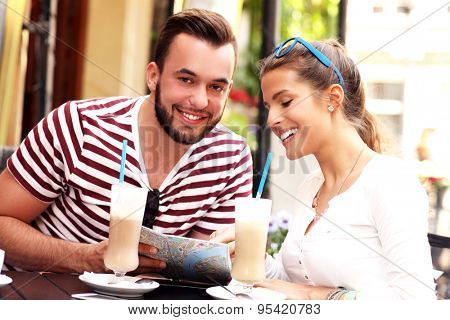 A picture of a couple of tourists drinking frappe in a cafe