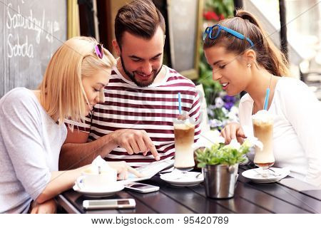 A picture of a group of tourists looking at map in a cafe