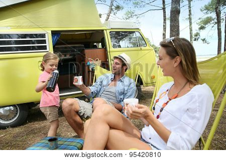 happy family relaxing by camper van in summer