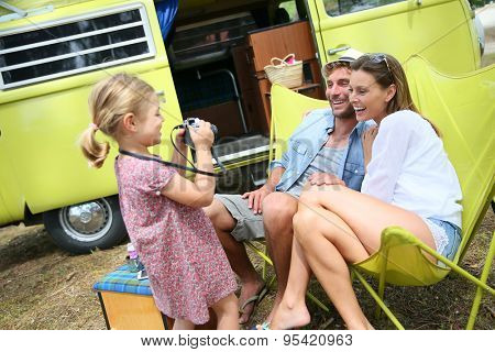 Little girl taking picture of her parents on campground