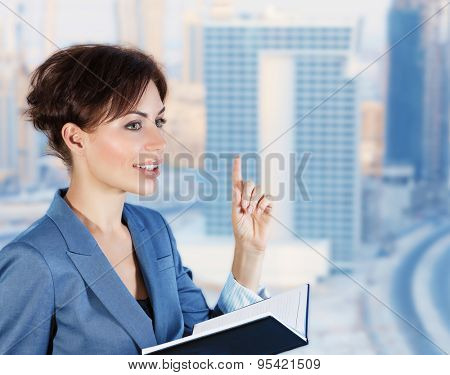 Beautiful business woman in an office with windows overlooking the luxurious new buildings, holds a meeting with colleagues, successful career of young people