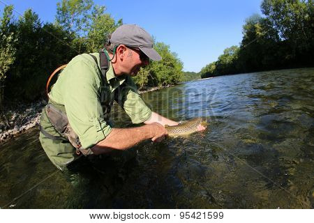 Fisherman releasing trout in river
