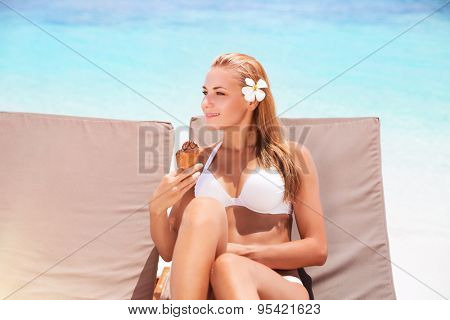 Beautiful woman on the beach, pretty girl sitting on sunbed with two ice cream in hand waiting for her boyfriend, female enjoying summer vacation on tropical resort