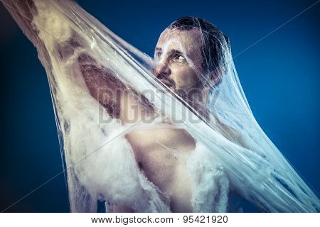 Tangled, naked man trapped in a huge spider web