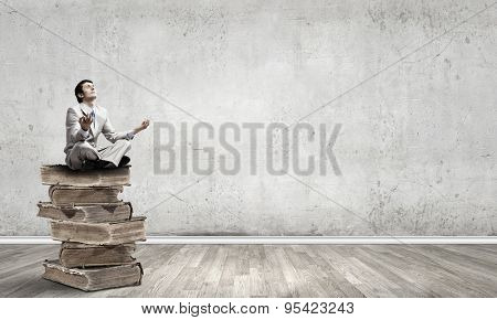 Young businessman sitting on pile of old books and meditating
